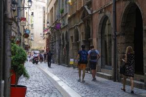 Passants dans rue pavée du Vieux Lyon